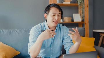 ung asiatisk affärsman bär hörlurar med bärbar dator prata med kollegor om planering i videosamtal medan du arbetar hemifrån i vardagsrummet. självisolering, social distansering, karantän för förebyggande av covid. foto