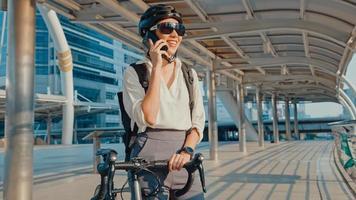 asiatisk affärskvinna med ryggsäck samtal mobiltelefon prata leende i stadsgatan gå till jobbet på kontoret. sportflicka använder sin telefon för att arbeta. pendla till jobbet med cykel, affärspendlare i staden. foto