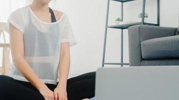 ung koreansk dam i sportkläder övningar som tränar och använder bärbar dator för att titta på yoga video tutorial hemma. avlägsen utbildning med personlig tränare, social distans, online utbildningskoncept. foto