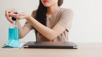 asiatisk kvinna som använder alkoholgel handdesinfektionsmedel tvätta handen innan den öppna tabletten för att skydda coronaviruset. kvinnor pressar alkohol för att städa för hygien när social distans stannar hemma och självkarantän foto