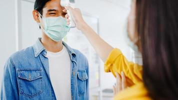 asiatisk kvinnlig receptionist som bär skyddande ansiktsmask använder infraröd termometerchecker eller temperaturpistol på kundens panna innan de kommer till kontoret. livsstil ny normal efter corona -virus. foto