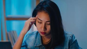 tusenårig ung kinesisk affärskvinna som arbetar sent på kvällen stressar med projektforskningsproblem på bärbar dator i vardagsrummet i modernt hem. asien människor koncept för yrkesmässig utbrändhet. foto