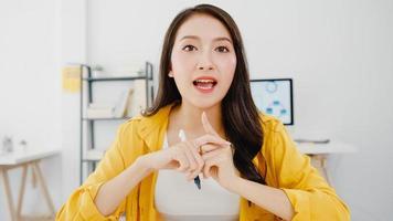 asiatisk affärskvinna social distansering i en ny normal situation för att förebygga virus och titta på kamerapresentationer för vänner om planering i videosamtal medan de arbetar på kontoret. livsstil efter corona -virus. foto
