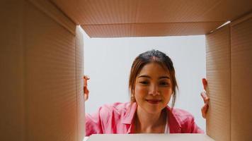 upphetsad asiatisk ung kvinna packar upp den stora kartongen och tittar in i en ny gåva hemma. glad millennial kvinnlig kund nöjd med beställt köp. leverans och online shopping koncept. foto