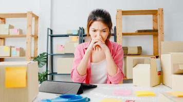 ung asien entreprenör affärskvinna kontrollera produkt inköpsorder på lager, med hjälp av surfplatta hårt arbete överbelastning på hemmakontoret. småföretagare, onlinemarknadsleverans, livsstil frilansande koncept. foto