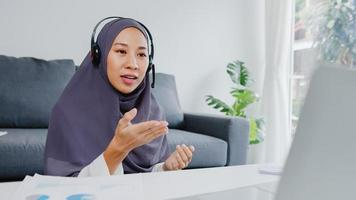 asien muslimsk dam bär hörlurar med bärbar dator prata med kollegor om planering i konferens videosamtal medan du arbetar hemma i vardagsrummet. social distansering, karantän för förebyggande av corona -virus. foto