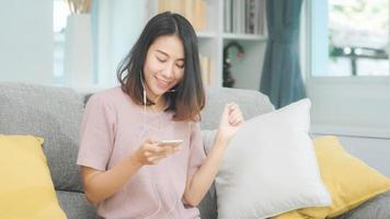 asiatisk kvinna som lyssnar musik och använder smart telefon, kvinnan använder slappningstid som ligger på hemmasoffan i vardagsrummet hemma. glad kvinnlig lyssnar musik med hörlurar koncept. foto