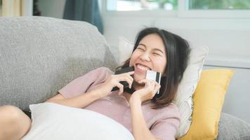 ung leende asiatisk kvinna som använder smartphone och köper onlineshopping med kreditkort medan hon ligger på soffan när hon kopplar av i vardagsrummet hemma. livsstil latin och spansktalande etnicitet kvinnor hemma koncept. foto