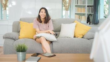 ung asiatisk tonårskvinna som tittar på tv hemma, kvinnlig känner sig lycklig liggande på soffan i vardagsrummet. livsstil kvinna koppla av på morgonen hemma koncept. foto