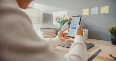 ung asiatisk dam använder mobiltelefon för att handla produkt online och betala räkningar med bankapp med transaktion lyckad. stanna hemma, karantänaktivitet, rolig aktivitet för förebyggande av coronavirus. foto