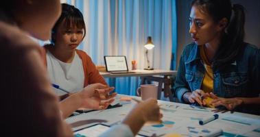 närbild asien affärsmän möte plan analys statistik brainstorm och huvudet på teamet hålla tablett punkt graf diagram och anställd notera på hemmakontoret natt. finansstrategi framgång koncept. foto
