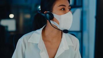 tusenåriga asien unga call center team eller kundsupport verkställande bär ansiktsmask förhindra covid-19 med hjälp av dator och mikrofon headset fungerar teknisk support i sen natt kontor. foto
