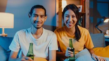glada unga asiatiska par tittar på kameran njuta av nattfest händelse online sitta soffan videosamtal med vänner toast dricka öl via videosamtal online i vardagsrummet hemma, social distansering koncept. foto
