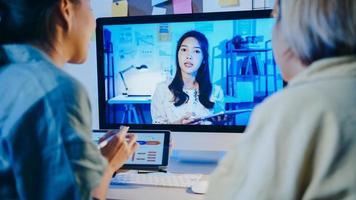 asiatiska affärskvinnor som använder skrivbord pratar med kollegor om planering i videosamtalsmöte i vardagsrummet. arbeta från huset överbelastning på natten, distansarbete, social distansering, karantän för coronavirus. foto