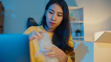 ung asiatisk affärskvinna förpackningsglas använder bubbelplast för packning stöd skada ömtålig produkt på hemmakontor på natten. småföretagare, onlinemarknadsleverans, livsstil frilansande koncept. foto