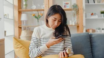 sjuk ung asiatisk kvinna hålla medicin sitta på soffan ta foto skickas till läkare hemma. tjej tar medicin efter läkarorder, karantän hemma, coronavirus socialt distanserat karantänbegrepp.