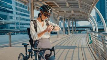asiatisk affärskvinna med ryggsäck cykel le smartwatch i stadsgatan gå till jobbet på kontoret. sportflicka använder sin klockapp för fitnessspårning. pendla till jobbet, affärspendlare i staden. foto