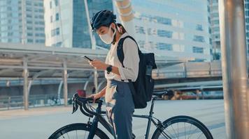 asiatisk affärskvinna bär ryggsäck bär antivirusskyddsmask ta cykelpromenad och kolla telefonen i stadsgatan gå till jobbet på kontoret. pendla till jobbet, affärspendlare för covid-19-konceptet. foto