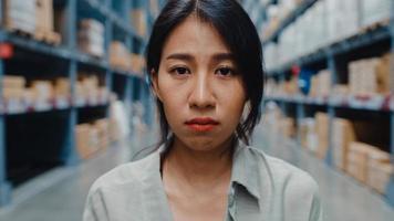 olycklig ung Asien affärskvinna chef ser och känner sig förvirrad, klia sig i huvudet, uttrycker tvivel stå i detaljhandeln köpcentrum. distribution, logistik, paket redo för leverans. foto