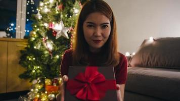 ung asiatisk kvinna som använder mobiltelefons videosamtal och pratar med par med julklappslåda, julgran dekorerad med prydnad i vardagsrummet hemma. julkväll och nyårsfest foto