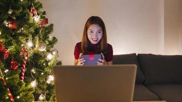 ung asiatisk kvinna som använder bärbara videosamtal och pratar med par med julklappslåda, julgran dekorerad med prydnad i vardagsrummet hemma. julkväll och nyårsfest. foto