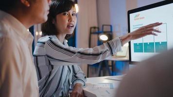 grupp asiatisk affärsman och affärskvinna som använder datorpresentation och kommunikationsmöte brainstorming idéer om nya projektkollegor som arbetar med plan för framgångsstrategi på nattkontor. foto