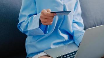 ung asiatisk dam med bärbar dator, kreditkort köper och köper e-handel internet i vardagsrummet hemma. stanna hemma, shoppa online, självisolering, social distansering, karantän för coronavirus. foto