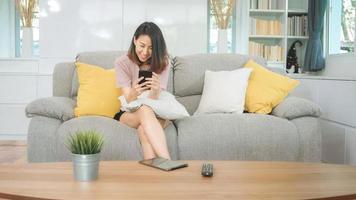 ung asiatisk kvinna som använder smartphone som kontrollerar sociala medier som känner sig lycklig leende medan hon ligger i soffan när hon kopplar av i vardagsrummet hemma. livsstil latin och spansktalande etnicitet kvinnor hemma koncept. foto