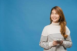 ung asiatisk dam med telefon med positivt uttryck, ler brett, klädd i vardagskläder som känner lycka och står isolerad på blå bakgrund. glad förtjusande glad kvinna jublar över framgång. foto