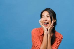ung asiatisk dam känner lycka med positivt uttryck, glädjande överraskning funky, klädd i avslappnad trasa isolerad på blå bakgrund. glad förtjusande glad kvinna jublar över framgång. ansiktsuttryck. foto