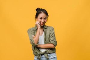 porträtt av ung asiatisk dam med positivt uttryck, korsade armar, le brett, klädd i vardagskläder och titta på kameran över gul bakgrund. glad förtjusande glad kvinna jublar över framgång. foto