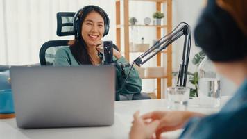 asien flicka radio värd spela in podcast använda mikrofon ha på sig hörlurar intervju kändis gäst innehåll konversation prata och lyssna i hennes rum. ljudpodd hemifrån, ljudutrustningskoncept. foto