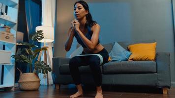 ung asiatisk dam i sportkläder som gör knäböjsträning som tränar i vardagsrummet hemma på natten. sport och rekreationsaktivitet, social distansering, karantän för att förebygga corona -virus. foto
