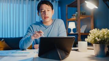 Asien affärsman fokus online videosamtal möte uppdrag på pappersarbete med kollega i surfplatta i vardagsrummet hemma övertid på natten, arbete hemifrån coronavirus pandemi koncept. foto