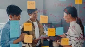 asiatiska affärsmän står bakom transparent glasvägg lyssnar chef pekar på framstegsarbete och brainstorm möte och arbetare post lappar på väggen på kontoret. affärsinspiration, dela idéer. foto