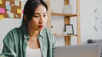 asiatisk affärskvinna som använder bärbar dator prata med kollegor om planering i videosamtal medan smart arbetar hemifrån i vardagsrummet. självisolering, social distansering, karantän för förebyggande av corona-virus. foto