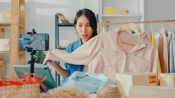 ung asiatisk dammodedesigner som använder mobiltelefon tar emot inköpsorder och visar kläder som spelar in video live streaming online i butik. småföretagare, online marknadsföringskoncept. foto