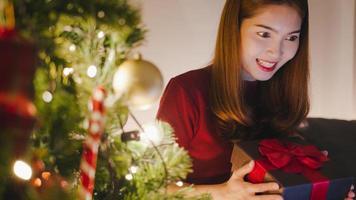 ung asiatisk kvinna som använder surfplatta videosamtal pratar med par med julklappslåda, julgran dekorerad med prydnad i vardagsrummet hemma. julkväll och nyårsfest. foto