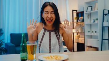 ung asiatisk dam som dricker öl som har roligt happy night party nyårshändelse online firande via videosamtal via telefon hemma på natten. social distans, karantän för coronavirus. synvinkel eller pov foto