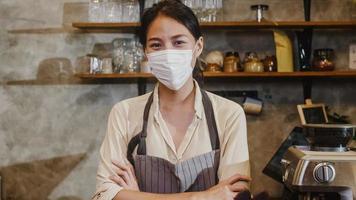 porträtt ung asiatisk tjej servitris bär medicinsk ansiktsmask känner glatt leende väntar på kunder efter lockdown på urbant café. ägare småföretag, mat och dryck, företag öppnar igen koncept. foto