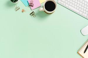 minimalt arbetsutrymme - kreativt plattläggningsfoto av arbetsytans skrivbord. ovanifrån kontorsbord med tangentbord och mus på pastellgrön bakgrund. ovanifrån med kopieringsutrymme, plattfotografering. foto