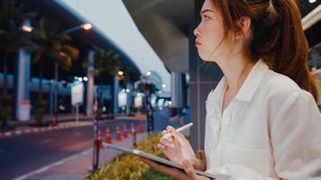 framgångsrik ung asiatisk affärskvinna i modekontorskläder med smart pennteknik för att skriva på digital surfplatta medan du sitter ensam utomhus i den urbana moderna staden på natten. business on the go -koncept. foto
