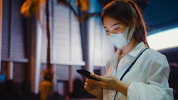 ung asiatisk affärskvinna i mode kontorkläder som bär medicinsk ansiktsmask med hjälp av smarttelefon som skriver textmeddelande medan du står utomhus i den urbana moderna staden på natten. business on the go -koncept. foto
