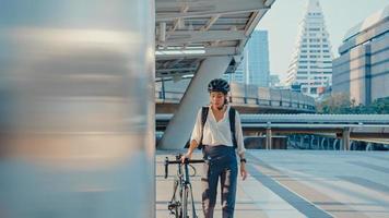 asiatisk affärskvinna gå till jobbet på kontorspromenad och le bär ryggsäck titta runt ta cykel på gatan runt byggnaden på en stadsgata. cykelpendling, pendling på cykel, affärspendelkoncept. foto