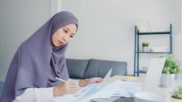 vacker asiatisk muslimsk dam i huvudduk casual wear med bärbar dator i vardagsrummet hemma. distansarbete hemifrån, ny normal livsstil, social distansering, karantän för förebyggande av corona -virus. foto