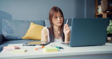 ung asiatisk tjej tonåring med avslappnad skjorta bär hörlurar använda bärbar dator lära sig online skriva föreläsning i bärbar dator i vardagsrummet hemma. isolera utbildning online e-learning coronavirus-pandemikoncept. foto