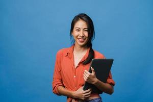 förvånad ung asiatisk dam håller bärbar dator med positivt uttryck, ler brett, klädd i vardagskläder och tittar på kameran på blå bakgrund. glad förtjusande glad kvinna jublar över framgång. foto