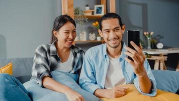 lyckliga unga asiatiska par man och kvinna sitter soffa använda smartphone facetime videosamtal med vänner och familj i vardagsrummet hemma. stanna hemma i karantän, social distansering, ungt gift koncept. foto