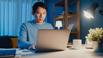 Asien frilans affärsman fokusera att skriva på bärbar dator online på distans från företaget på skrivbordet i vardagsrummet hemma övertid på natten, arbeta hemifrån under covid-19-pandemikonceptet. foto