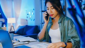 frilansande asiatiska kvinnor som använder bärbar dator pratar i telefon upptagen entreprenör som arbetar avlägset i vardagsrummet. arbeta från huset överbelastning på natten, distansarbete, social distansering, karantän för coronavirus. foto